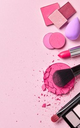 Girl's makeup essentials kit on pink background