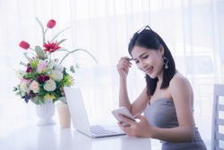 girl's using smart phone and working on laptop ,happy time on work, smile and laughing time work , workingwomen get think about work