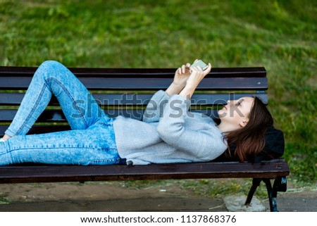 Girl schoolgirl. In summer, he lies on a bench in the city. In the hands of holding a smartphone, watching a video. Concept of rest after school. Emotion is a pleasure pleasure. #1137868376
