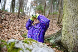 Girl scout looking through the binoculars in a forest, inspecting the surroundings and bird watching