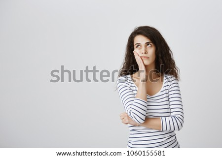 Girl screaming internally from boredom. Cute emotive curly-haired caucasian female making facepalm and rolling eyes from annoyance, hearing nonsense or boring conversation, standing over gray wall