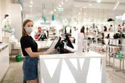 Girl seller in a mask and gloves stands at the checkout in a store. Store seller during COVID-19. Safety during the virus. The seller in the clothing store.