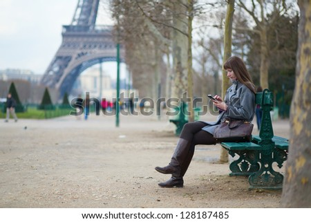 Girl sending sms or surfing in the net in Paris