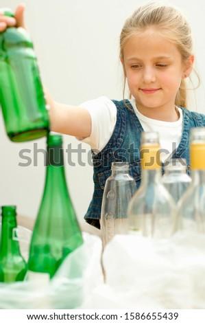 Girl separating green plastic bottle clear glass bottle, Den Haag, Netherlands