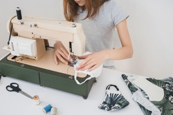 Girl sewing protective medicine mask on sewing machine at home to prevent the flu. Covid-19 in the room with white background home workplace