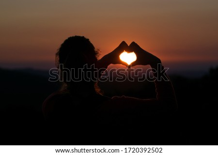 Photo of  Girl shaping hearth symbol with hands at beautiful romantic sunset. Hands in hearth shape around the sun. Romantic sunset with loved one. Sunset on a mountain.