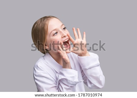 Girl shout. Little lady scream about sale. Looking side. Pretty kid with hands near head. Child portrait. Modern loud. Positive emotion. Sound on. Yelling face. Rumor concept Foto stock ©