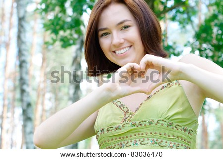 Girl showing a heart sign at the park  (with copy space)