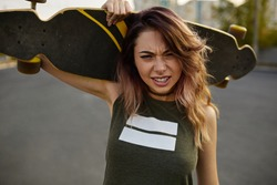 Girl showing attitude close up portrait, holding longboard on the shoulders. Hipster girl walking with the skate in the city. Extreme sport and emotions concept