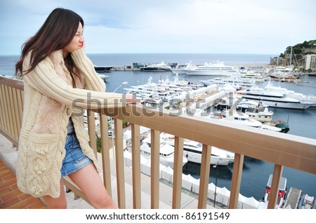 Girl showing funny face over the yacht harbor of Monte Carlo, Monaco