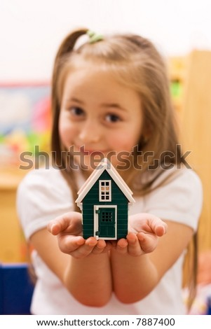 Girl showing her wish to their parents: a new home [focus on the house]