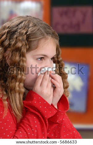 Girl showing proper hygiene by using a tissue to wipe her nose