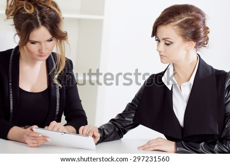 Girl showing something to her colleague, work in the office - Shutterstock ID 297231560