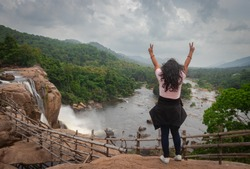girl showing victory and happiness at Athirapally waterfall with cloudy sky and green forests. It is falling from 80 mtrs high hill and it is the second largest waterfall in india.