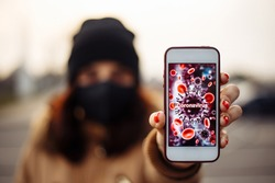 Girl shows a mobile phone with coronavirus sign. Young woman in city street wearing black sterile medical face mask. Quarantine COVID-19 pandemic coronavirus epidemic and health care concept