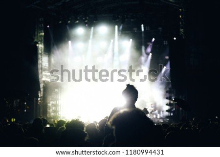 Girl silhouette in a crowd on someone's shoulders at open air night festival show #1180994431