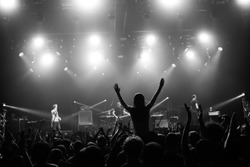 Girl silhouette in a crowd on someone's shoulders with the hands raised up at the concert in a club