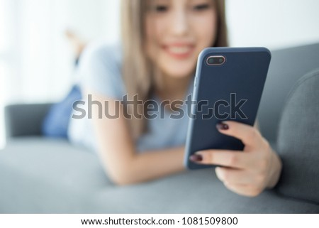 girl sit on couch using cellphone