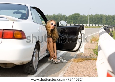 girl sits in the open car and dresses shoes