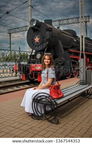 Girl sits on a bench near the vintage train. Woman with a red bag next to locomotive of the 19th - 20th century. Retro train made in USSR with a red star. Steam locomotive against cloudy sky.