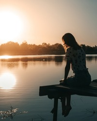 girl sits on a wooden pier near the water. sunset photo of a woman