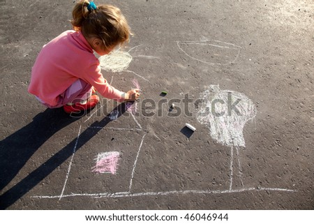 girl sits on concrete asphalt square road. girl draws painting line sun house tree a chalk on asphalt. child drawings paintings on asphalt concrete. back side view