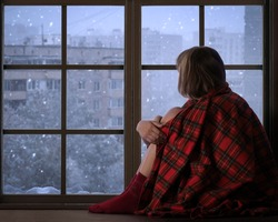 Girl sits on the window sill of the window and looks at the falling snow. The concept of home comfort, season, solitude