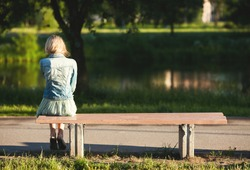 girl sitting alone on a bench