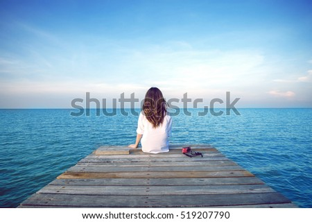 girl sitting alone on a the...