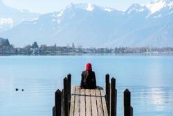Girl sitting alone on wooden Dock in Geneva lake, Switzerland