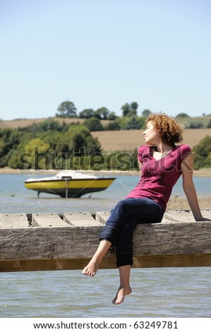 Girl sitting and sunbathing on landing stage in brittany