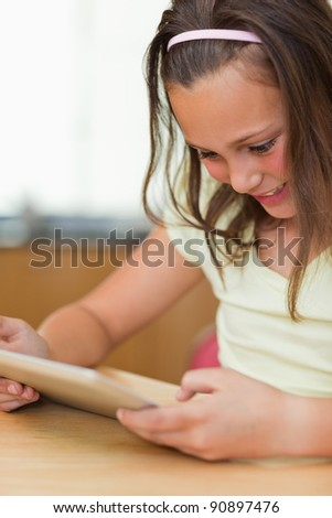 Girl sitting at the kitchen table while looking at tablet