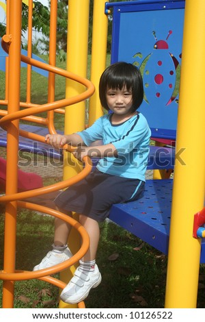 Girl sitting at the playground in the park