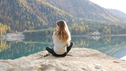 Girl sitting by mountain lake alpine area outdoors austria blue reflection forest beautiful view sunshine meditation selfcare mindfulness