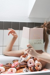 Girl sitting in a bath tub with donuts and reading a glamorous book