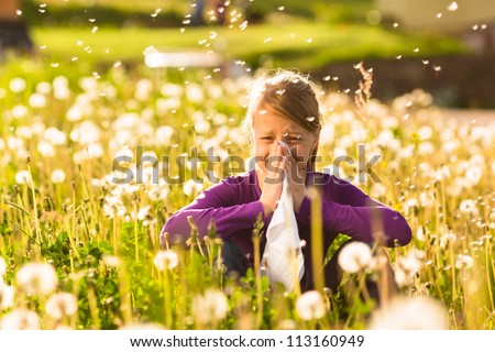 Girl sitting in a meadow with dandelions and has hay fever or allergy Stock photo ©