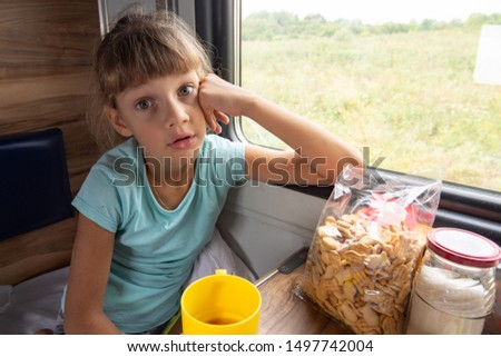 Girl sitting in a reserved seat carriage in a train funny looks in the frame