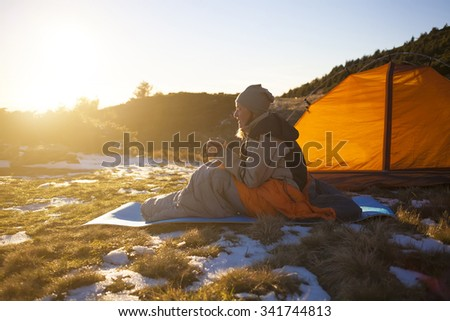 Girl sitting in a sleeping bag and drinking hot drink.