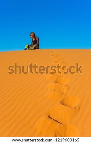 Girl sitting in Erg Chebbi Desert, Sahara Desert near Merzouga, Morocco