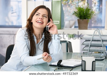 Girl sitting in office speaking on mobile phone, holding pen, laughing.