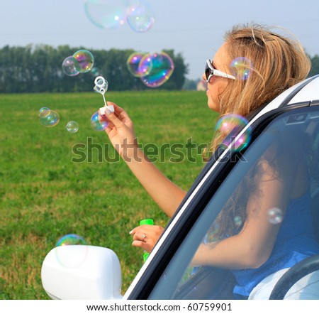 girl sitting in the car starts up soap bubbles. A closeup portrait