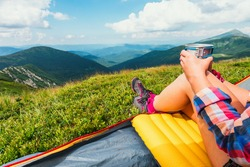 Girl sitting in they tent with hot tea against the backdrop of an incredible mountain landscape. Sunny day in highland