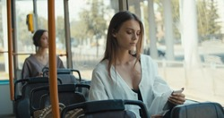 Girl sitting in tram using smartphone for chatting in social networks via free wifi connection, young woman reading phone on portable pc in public transport
