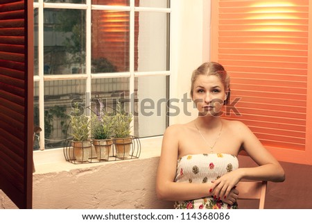 Girl sitting near an open window of the house