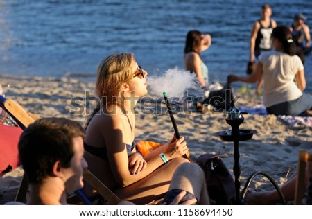 """Girl sitting on a beach and smoking a hookah, people on a background. Fest of Yoga and Vedic Culture """"Vedalife-2018"""". July 25, 2018. Kiev, Ukraine #1158694450"""