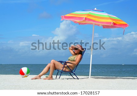 Girl sitting on a beach chair under an umbrella enjoying a sunny day at the beach.