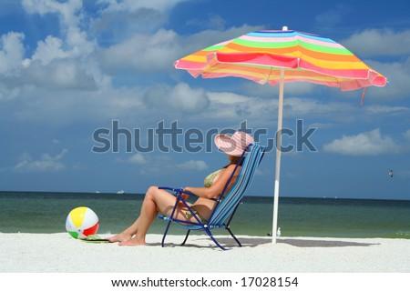 Girl sitting on a beach chair under an umbrella enjoying a sunny summer day at the beach