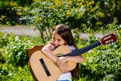 girl sitting on a chair with a guitar in nature