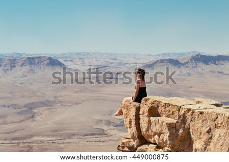 Girl sitting on a cliff and looking at desert Negev landscape. Summer vacation in Israel. #449000875