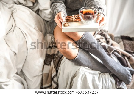 girl sitting on a cosy warm bed with tea and a book ,the concept of comfort and hipster #693637237